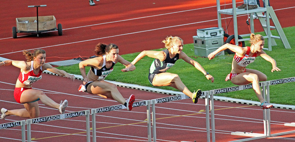 picture of hurdlers going over hurdles to illustrate overcoming objections to b2b products